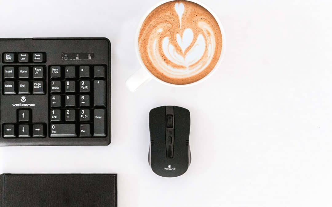 A computer mouse on a table with a cup of coffee.
