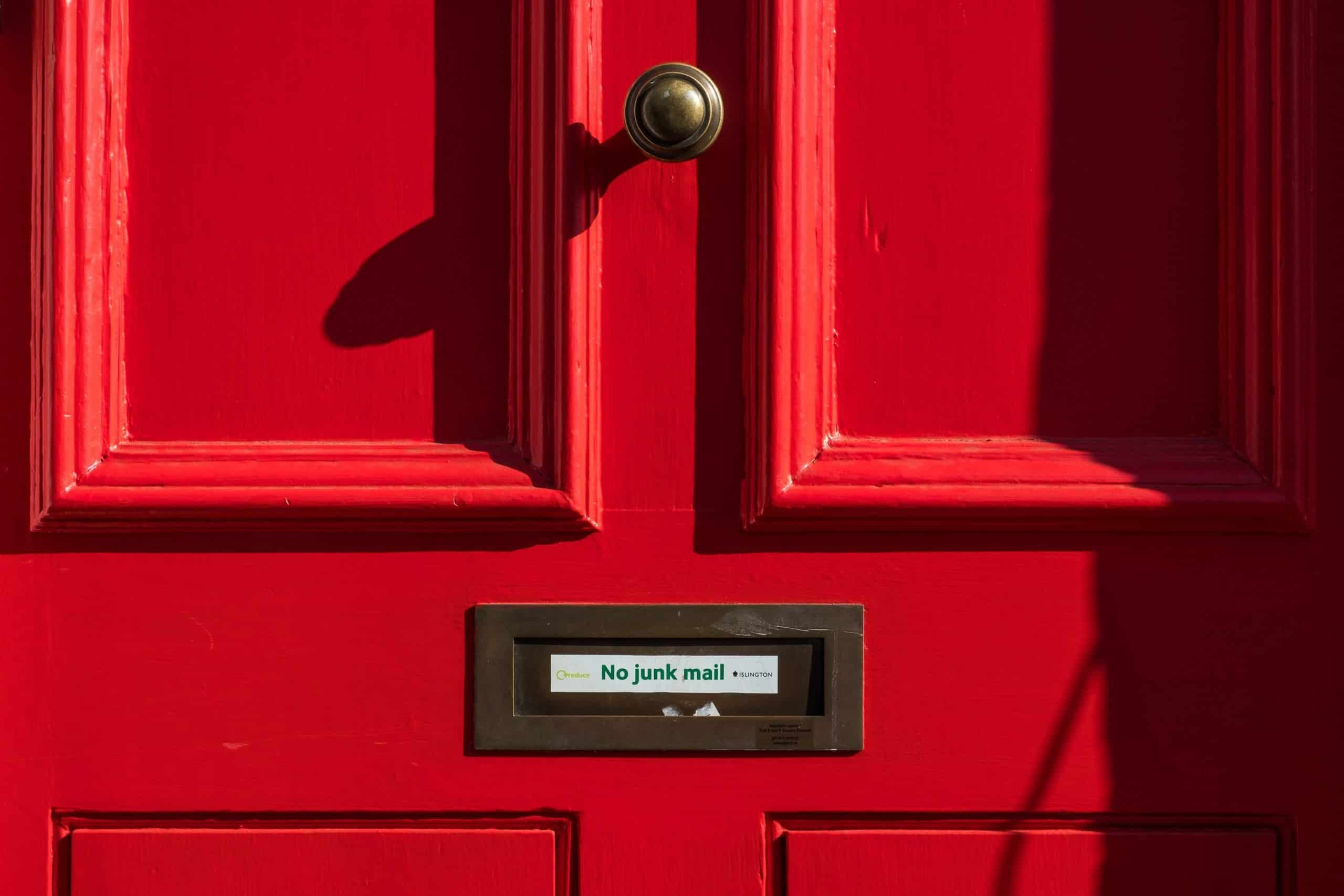 """Red door with letter slot that says """"no junkmail"""""""